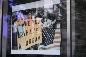 "Washington, USA. July 8, 2011. The reflaction of demonstrators on a window shop. Woman carrying a pancart with the image of Dr. King and the slogan ""We Too Have a Dream"" in reference to woman and Litino rights."